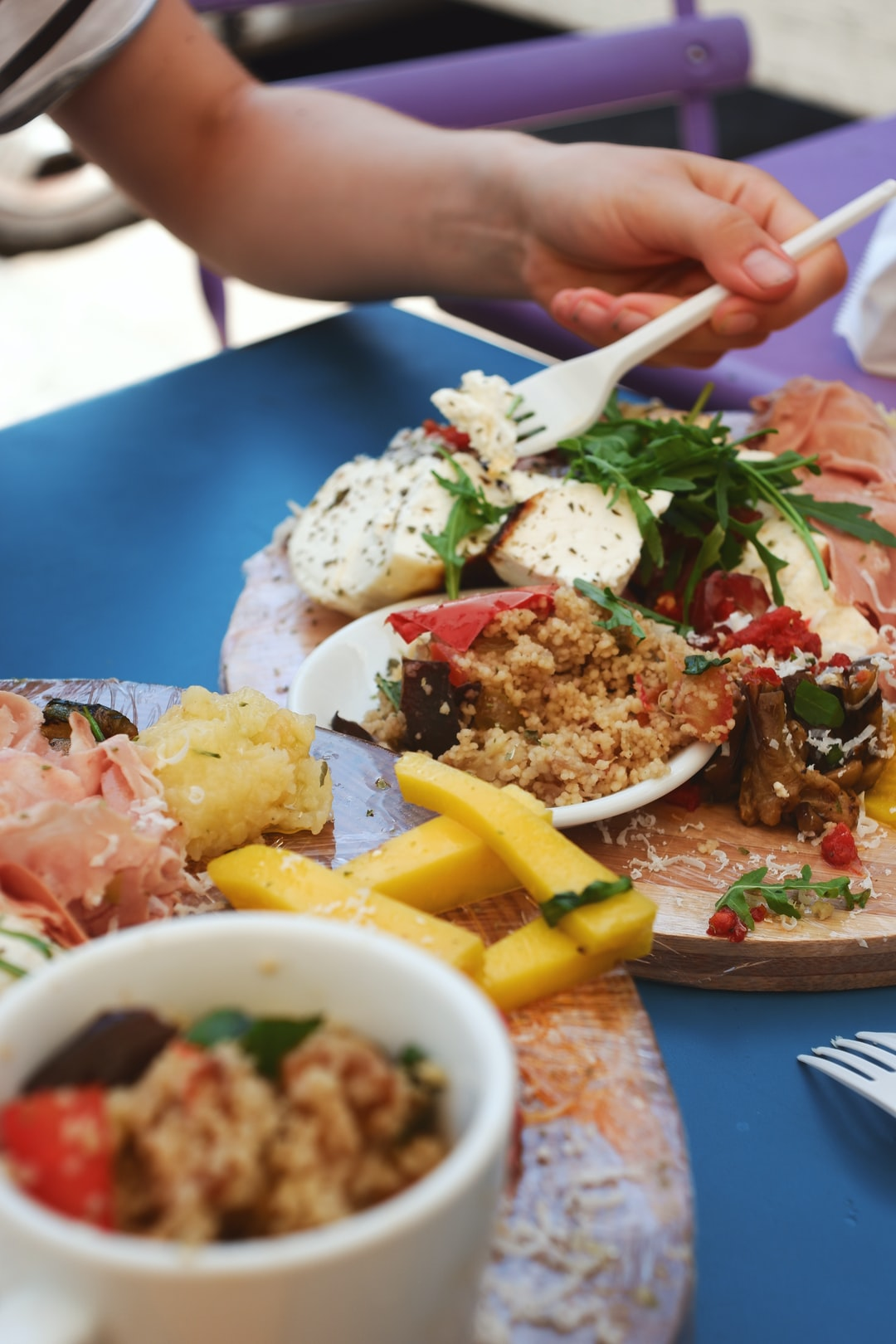 Italian food cheese and ham platter in Sicily with couscous, dried tomato and aubergine and arugula rocket salad