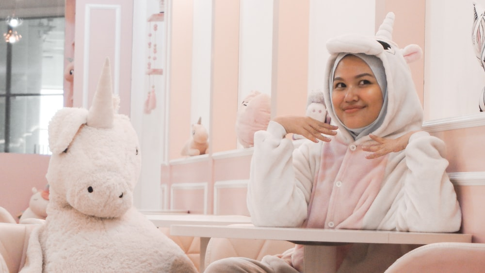 woman wearing white-and-pink unicorn costume sitting chair