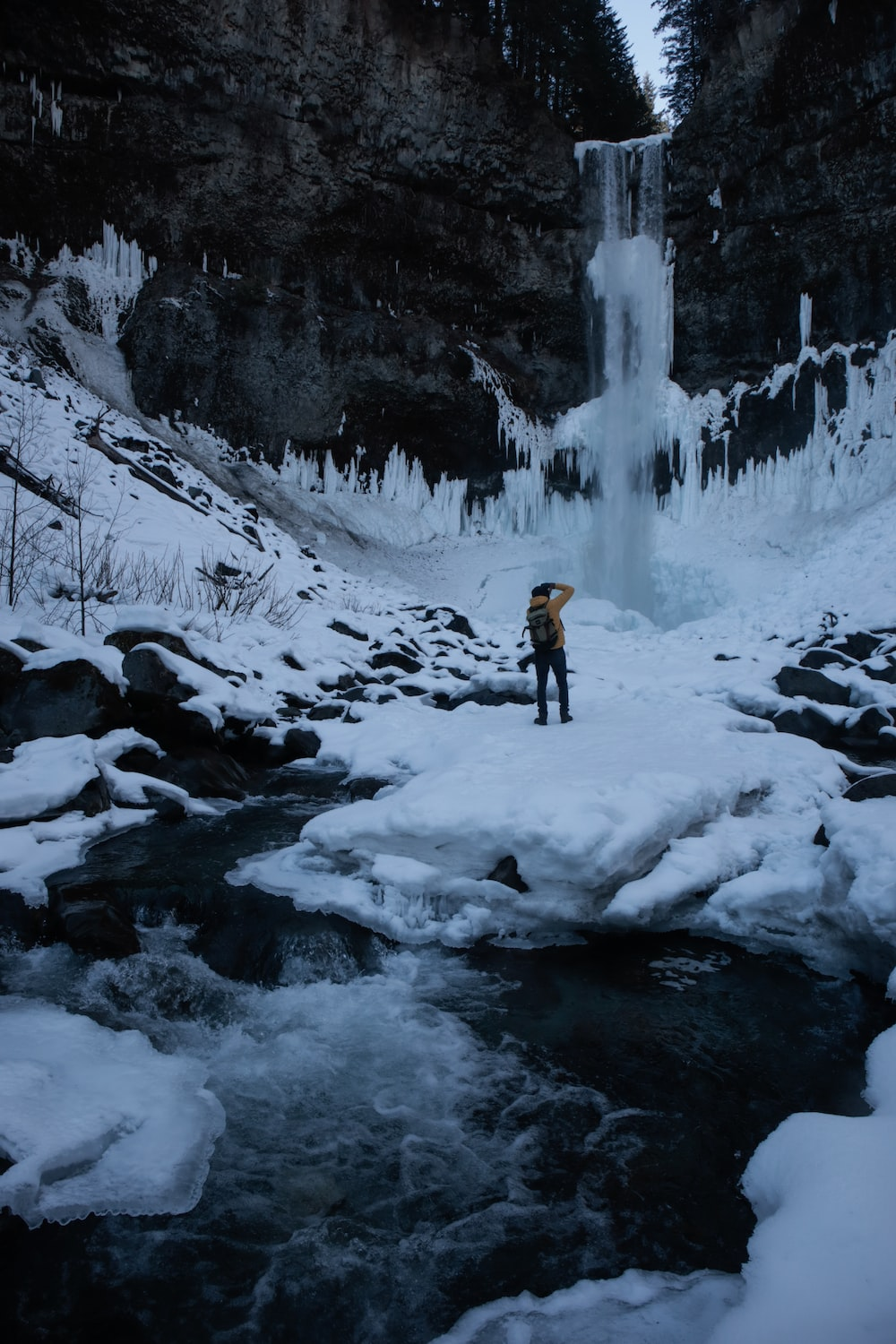 man standing on snow covered rock near waterfall