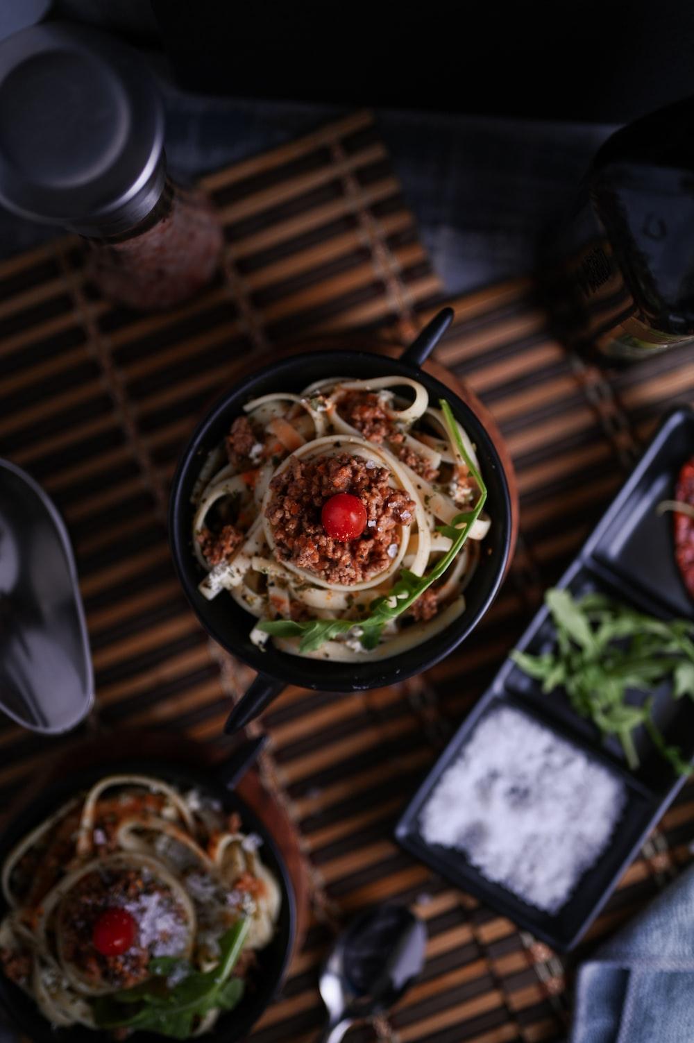black bowl with food near sauce bowl