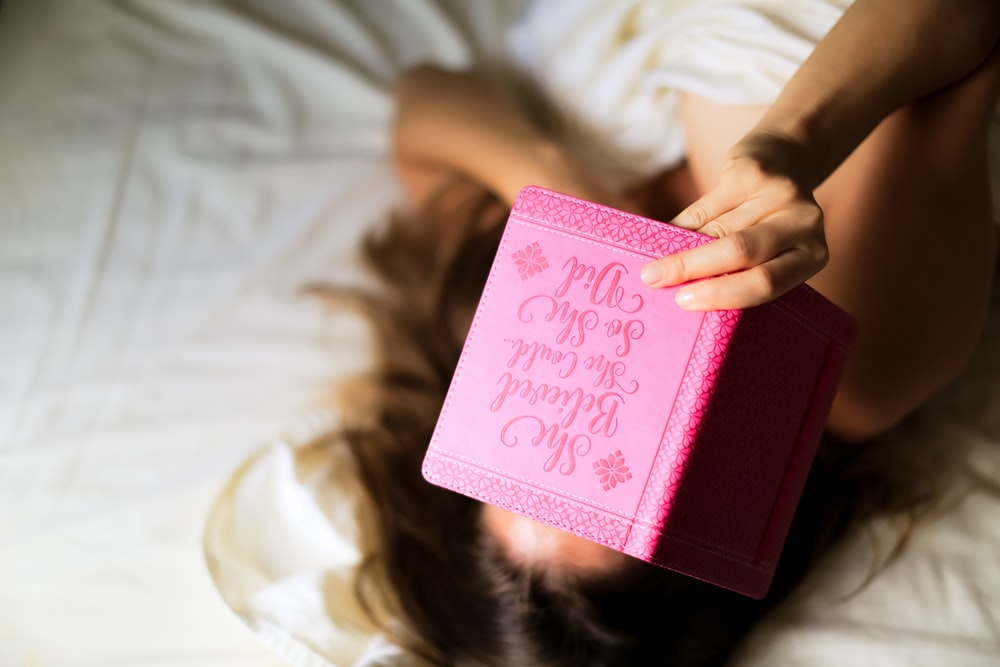 woman holding pink book