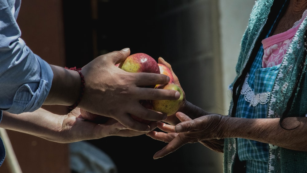 two persons holding fruits