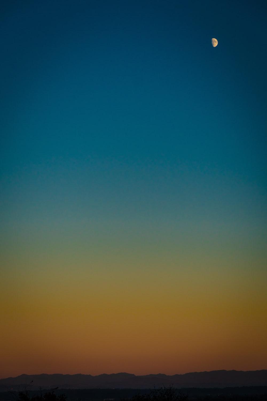 half moon in blue and orange sky
