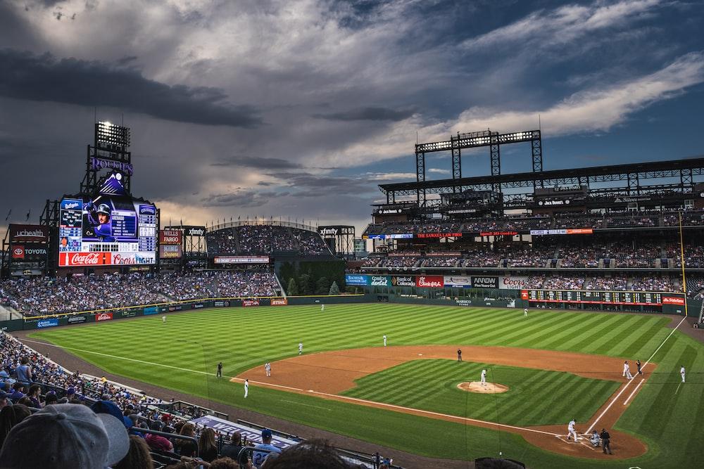 people in sports stadium watching baseball game