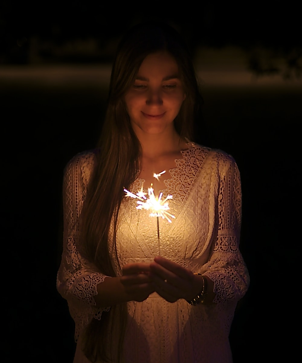 smiling woman wearing lighted sparkler