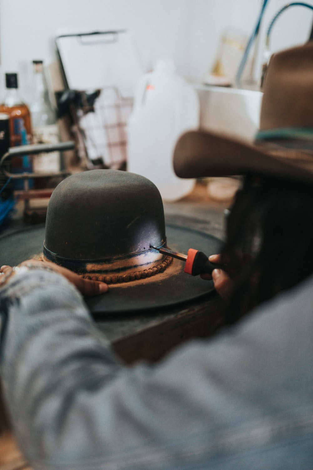 man fixing black and brown hat