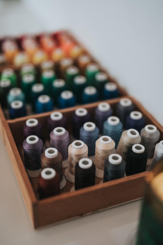 multicolored thread spools in brown wooden box