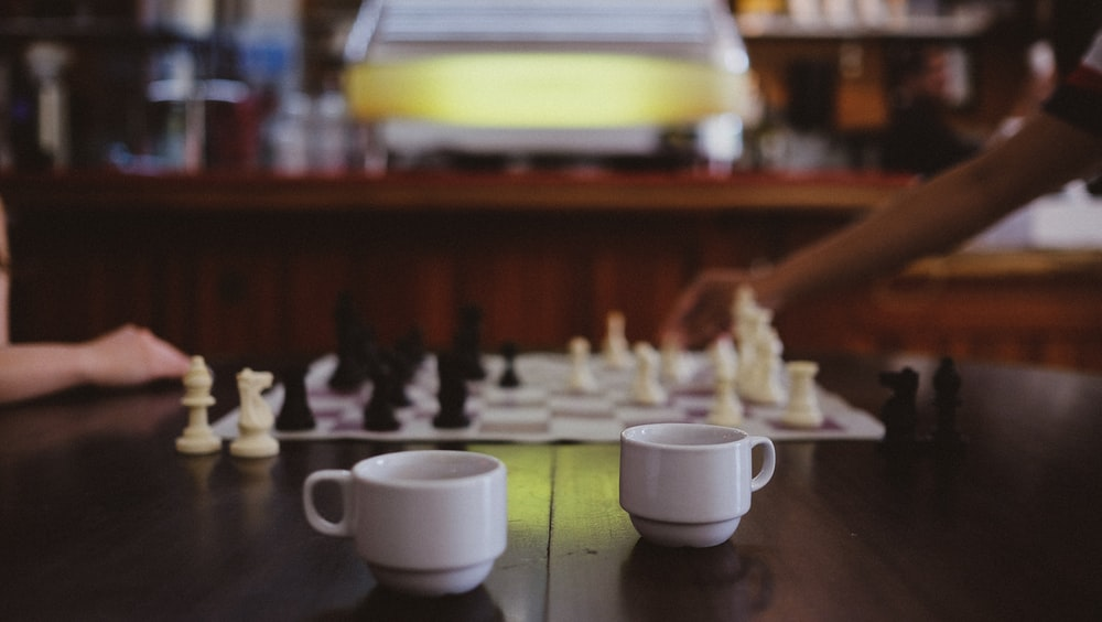 two white coffee cups on table near two people playing chess