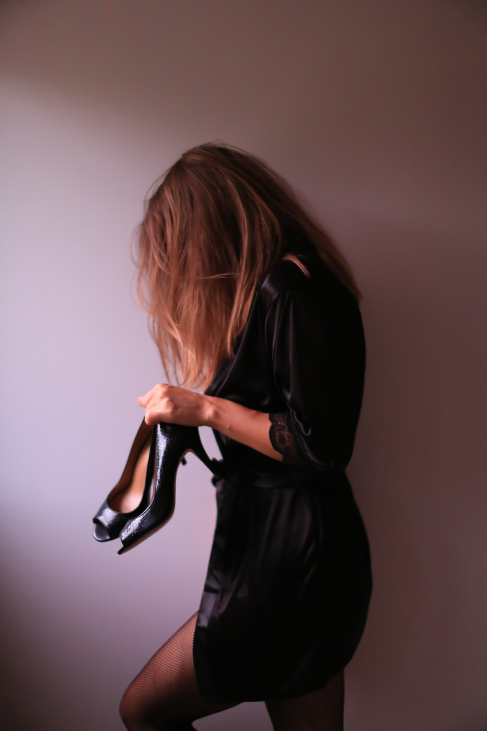 woman in black dress standing by the wall holding shoes