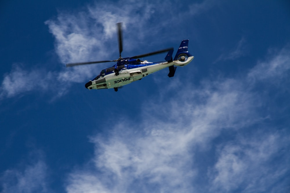 low-angle photography of white and blue helicopter