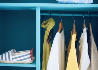 blue shelf with pair of slip-ons and five clothes