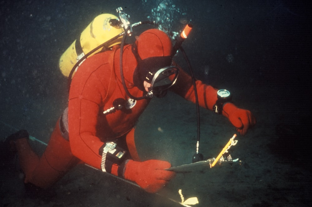 person in red wetsuit underwater