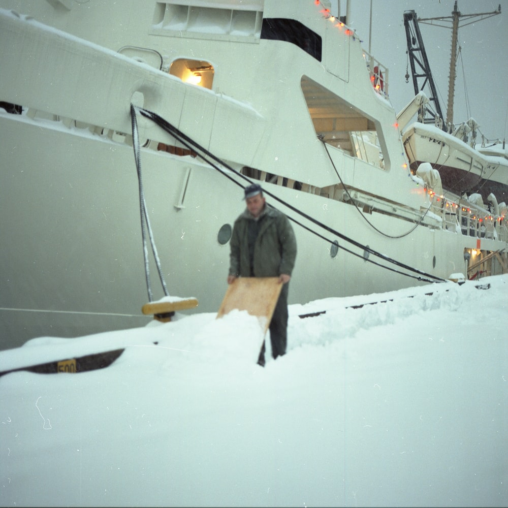 man standing on snow near boat during daytime