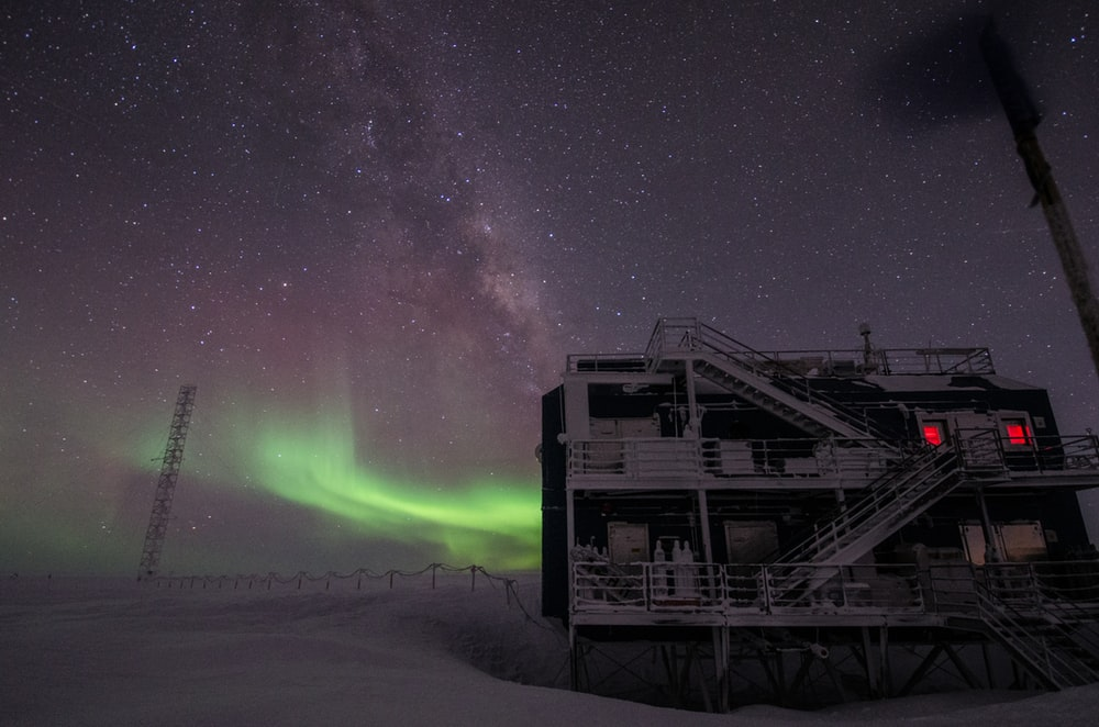 white multi-storey building under starry night and northern lights