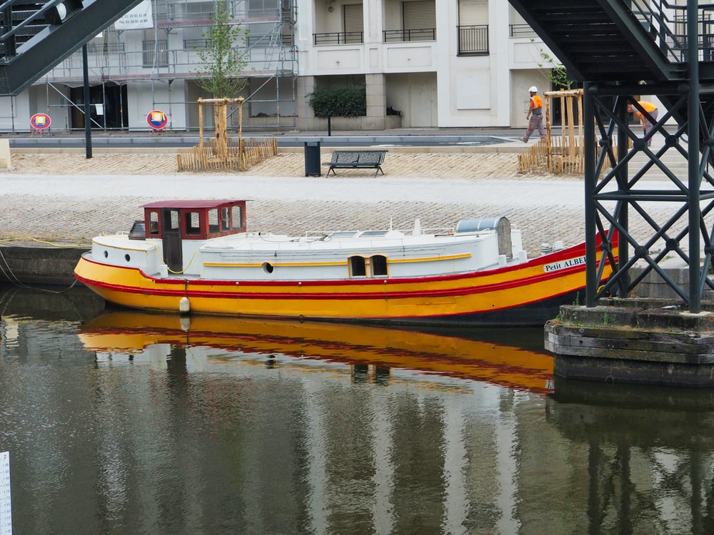 white and orange boat on body of water