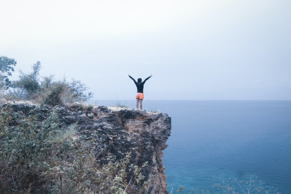 man in black and orange on a cliff