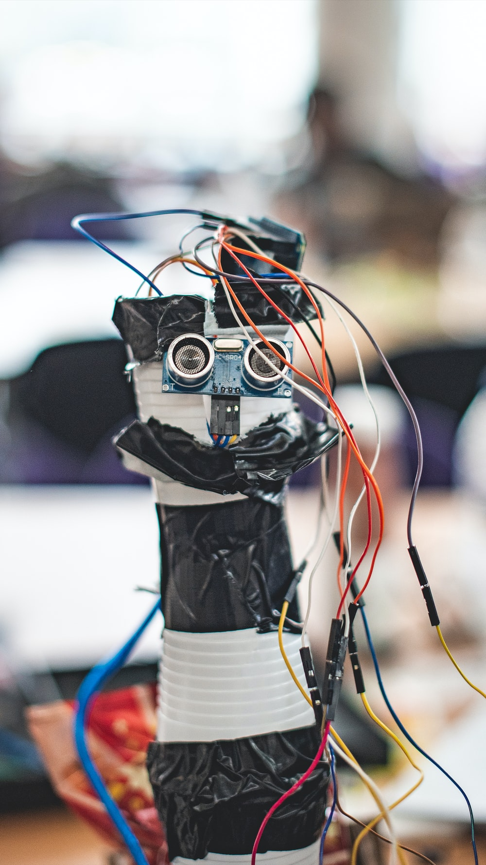 shallow focus photography of black and white robot