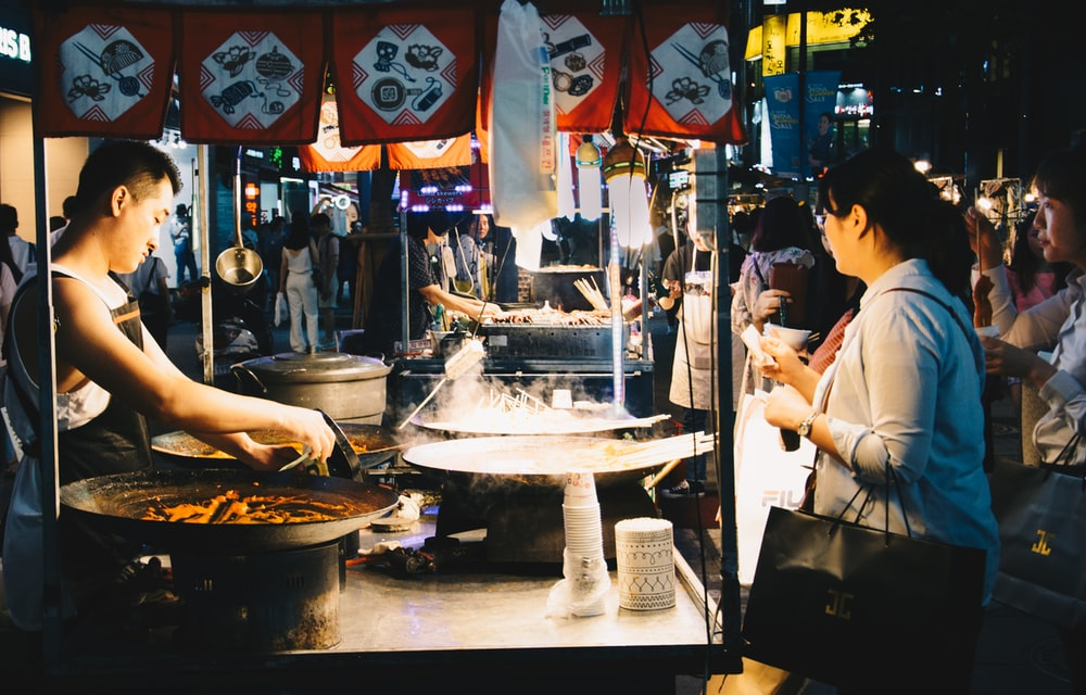 woman standing in front of food stall