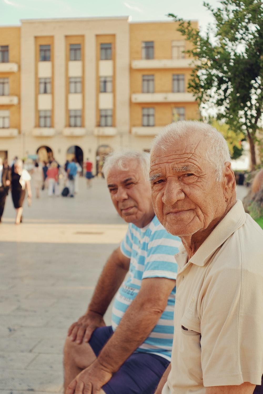 two men sitting near building during daytime