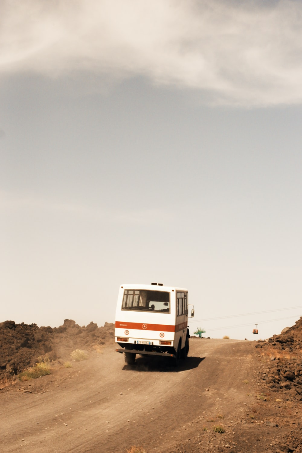 white and brown Mercedes-Benz van in dirt road