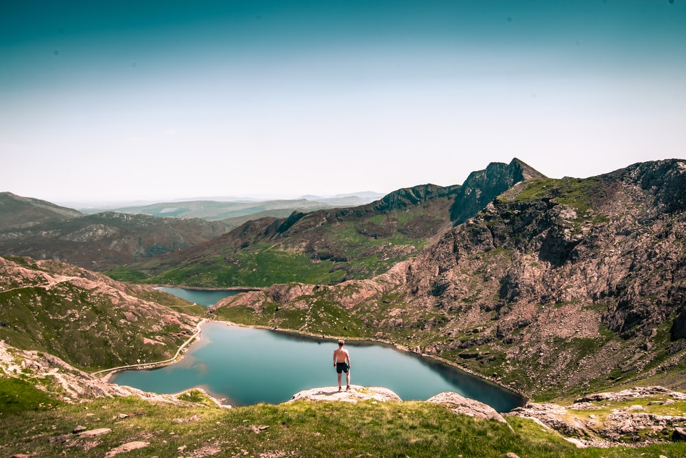 person standing on mountain beside lake during daytime