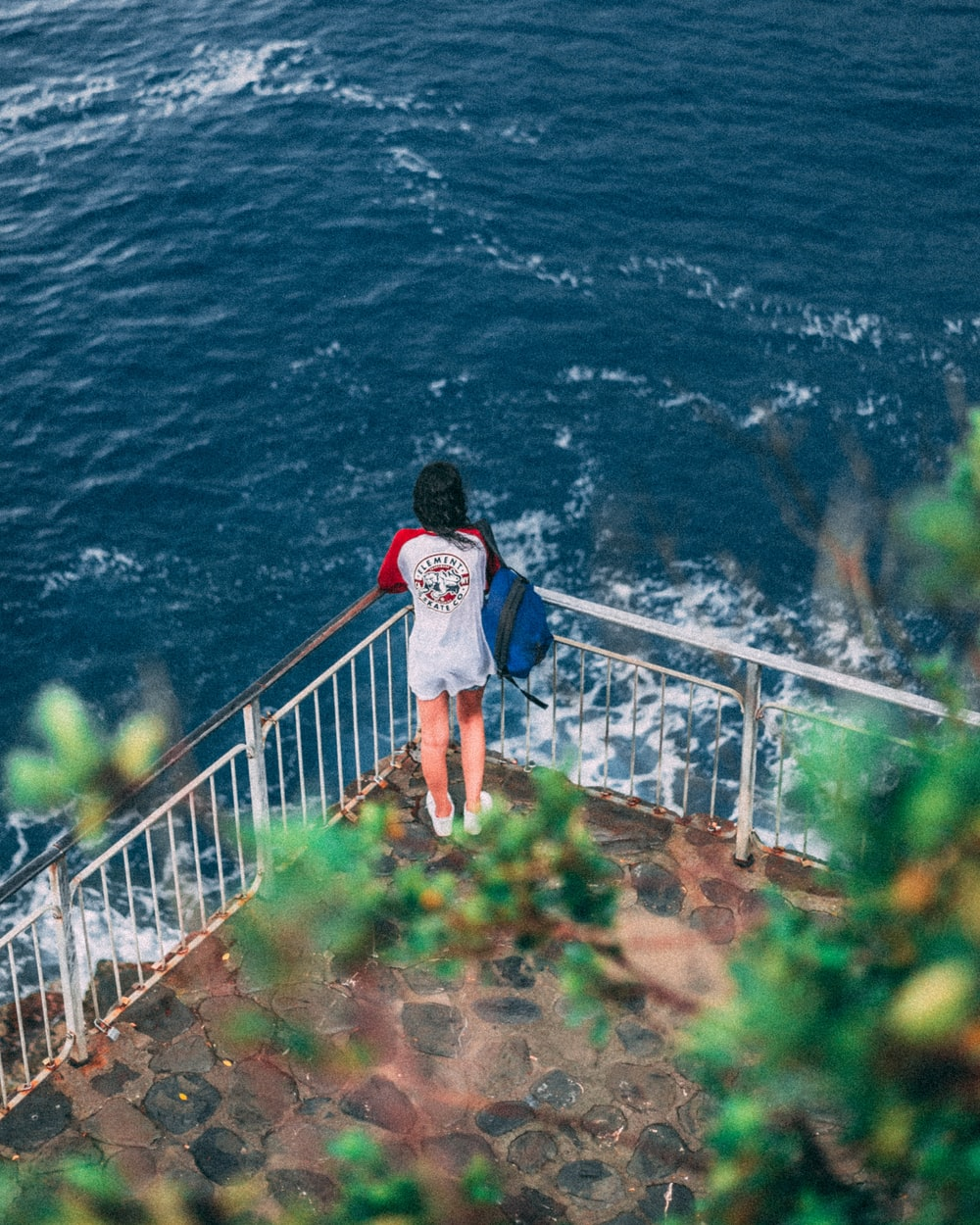 woman wearing red and white shirt looking at ocean