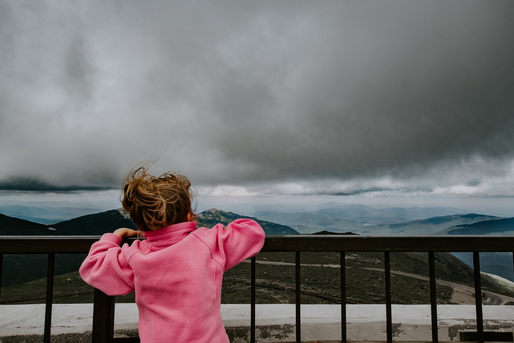 girl standing on railing under cloudy sky