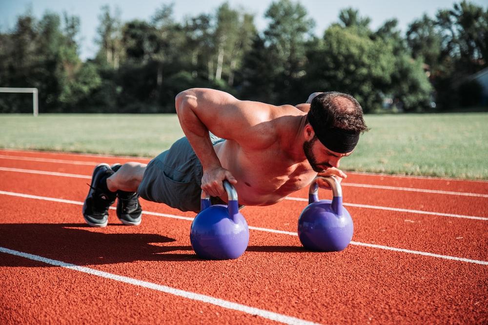 man exercising on field during daytime
