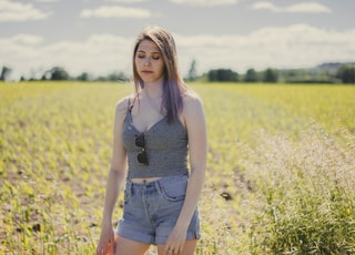 woman wearing gray crop top and blue denim short in the middle of grass field