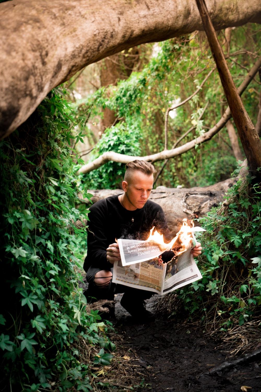 man in black crew-neck sweater holding burning newspaper