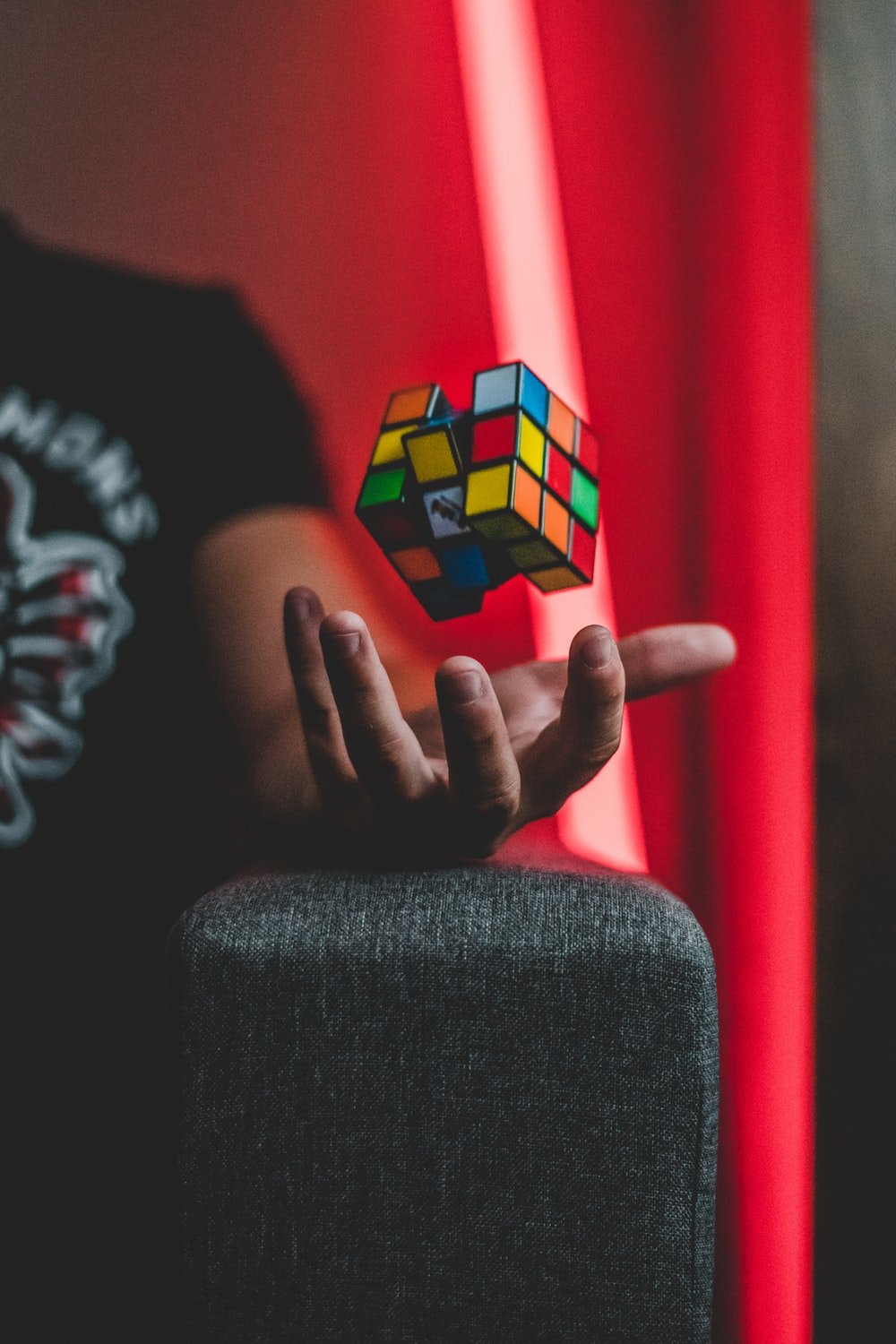 person tossing 3x3 Rubik's cube