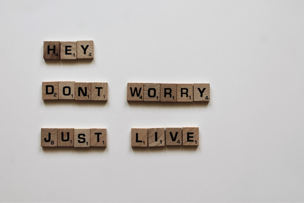 brown wooden game tiles saying hey don't worry just live