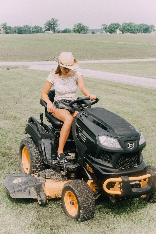 woman riding black riding mower