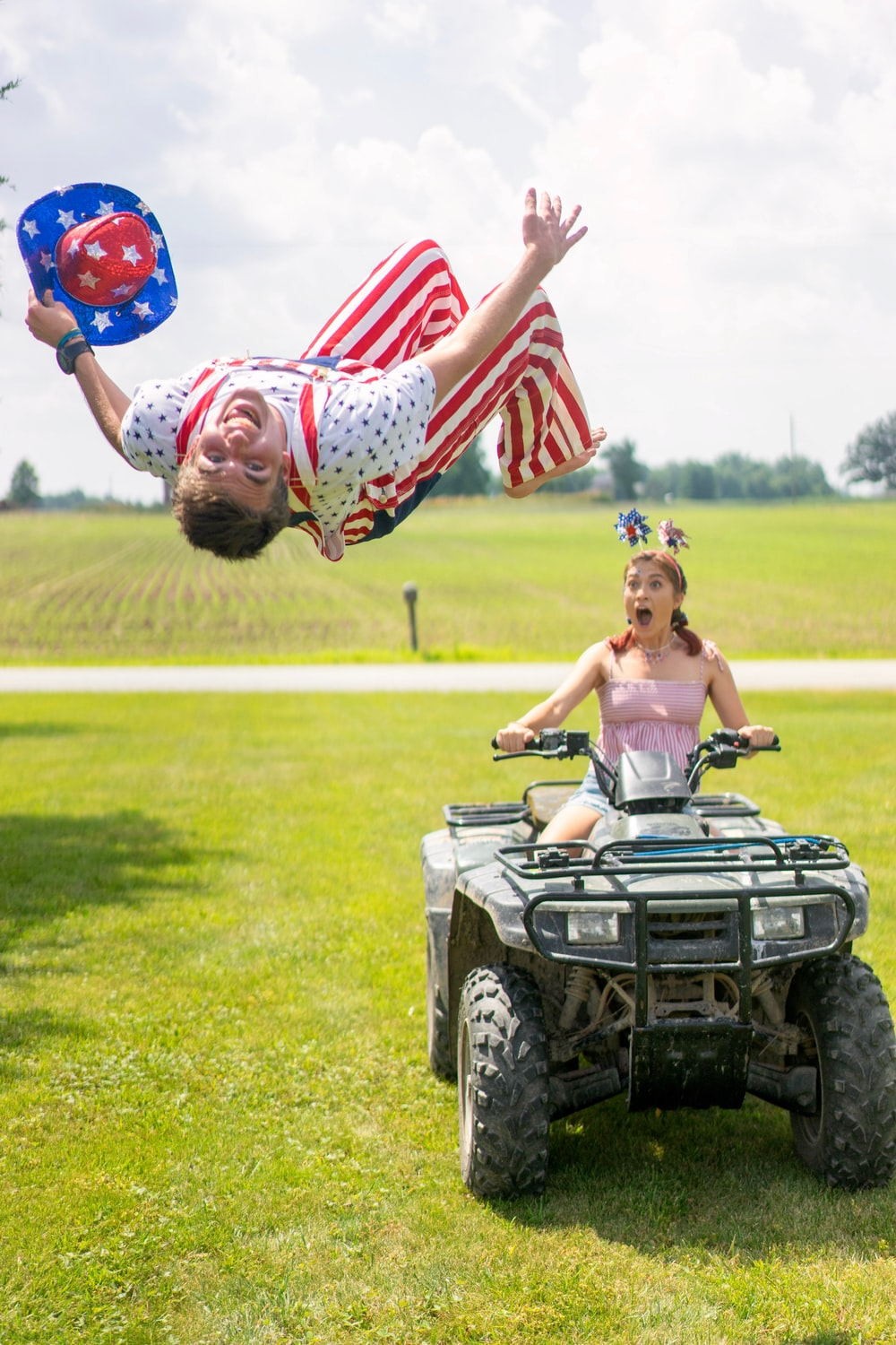 woman riding on ATV near man flying at the ground