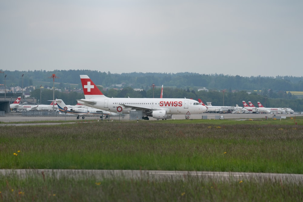 white and red Swiss airplane during daytime