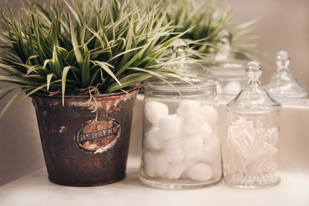 Vintage farmhouse decor on display in a bathroom, vintage advertising tin with faux green grass, apothecary jars with cotton balls and q-tips hold bathroom items in their pretty containers. An example of rustic, farmhouse home decor style.