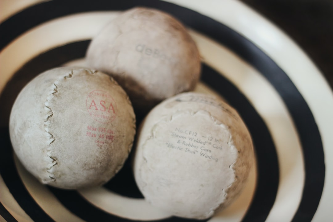 Detail of home decor, three vintage baseballs with stitching details are grouped together in a brown and ivory striped pottery bowl on a wooden table. Very vintage style, vintage decor, vintage decorating in neutral colors.