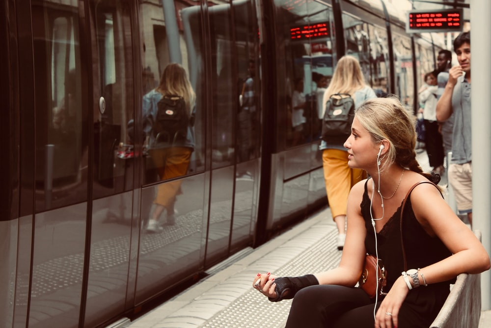 woman sitting on bench in front of train