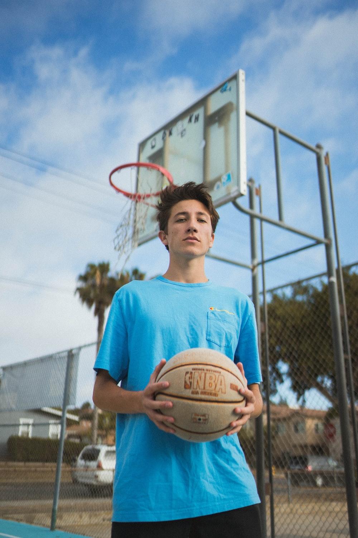 man holding basketball ball close-up photography