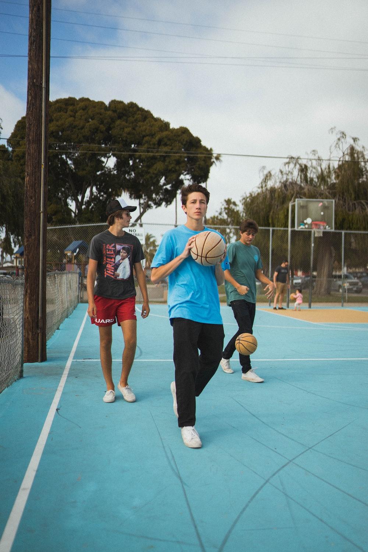 man wearing blue t-shirt and black pants holding basketball during daytime
