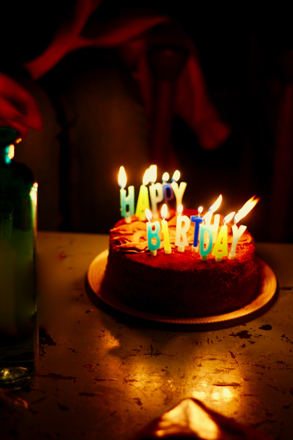 brown icing-covered cake with lighted candles