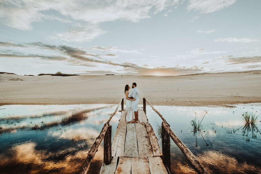 couple face each other on brown wooden dock