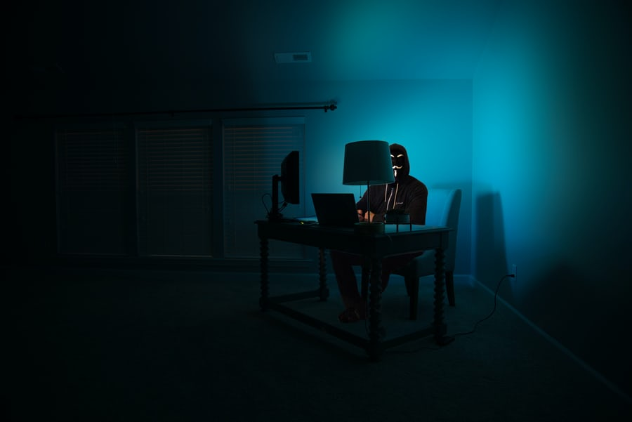 person wearing mask sitting at a computer desk