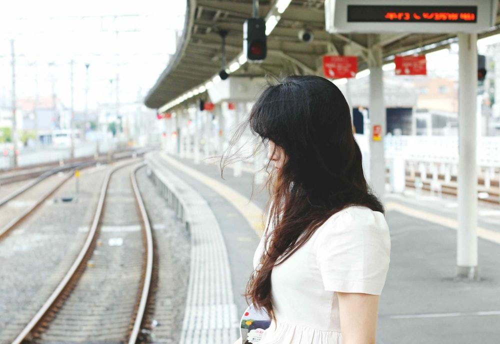 woman wearing white shirt standing beside train railway