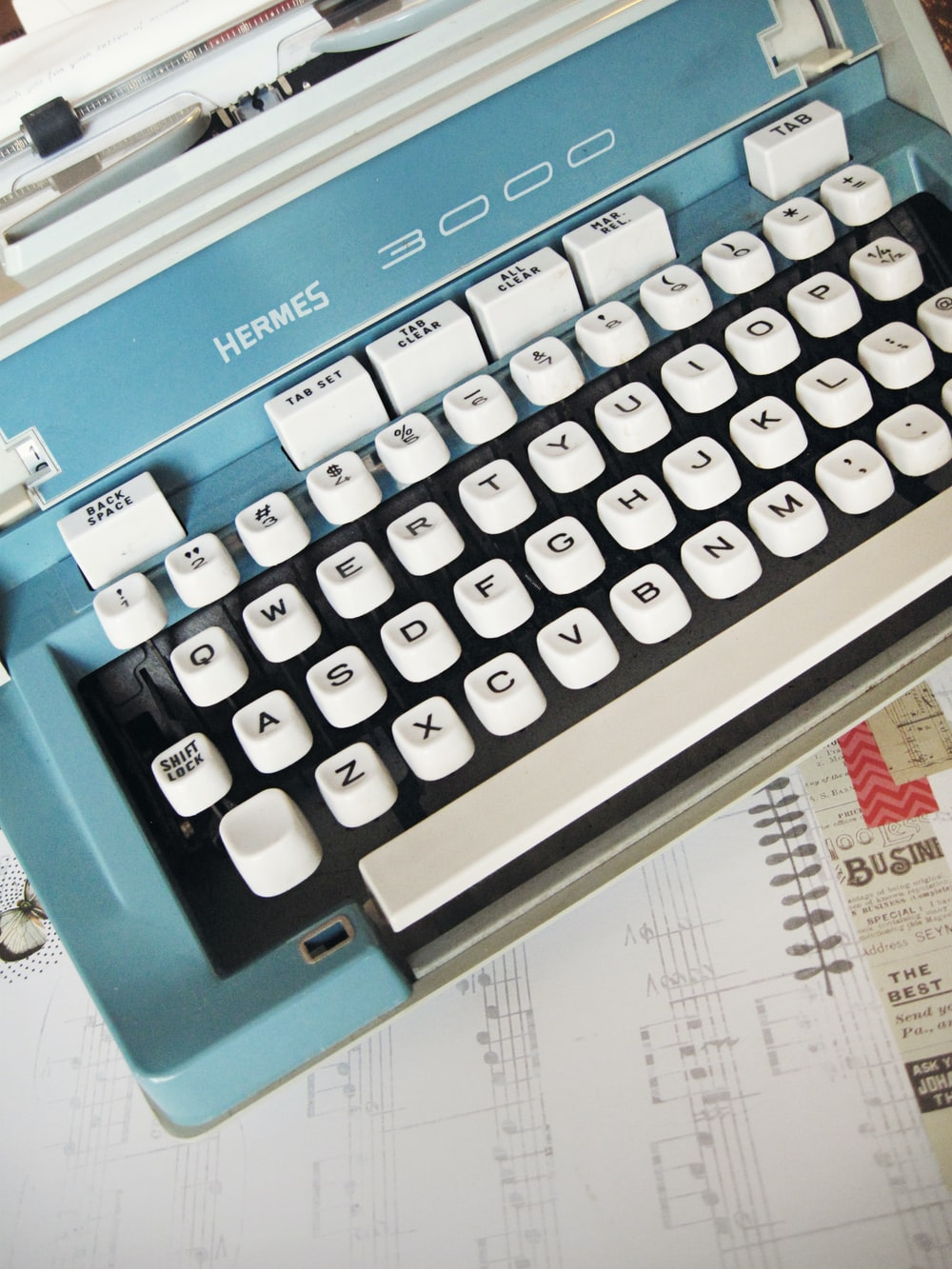 white and teal Hermes 3000 typewriter on white paper