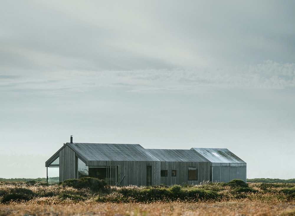 gray wooden building in the middle of the field