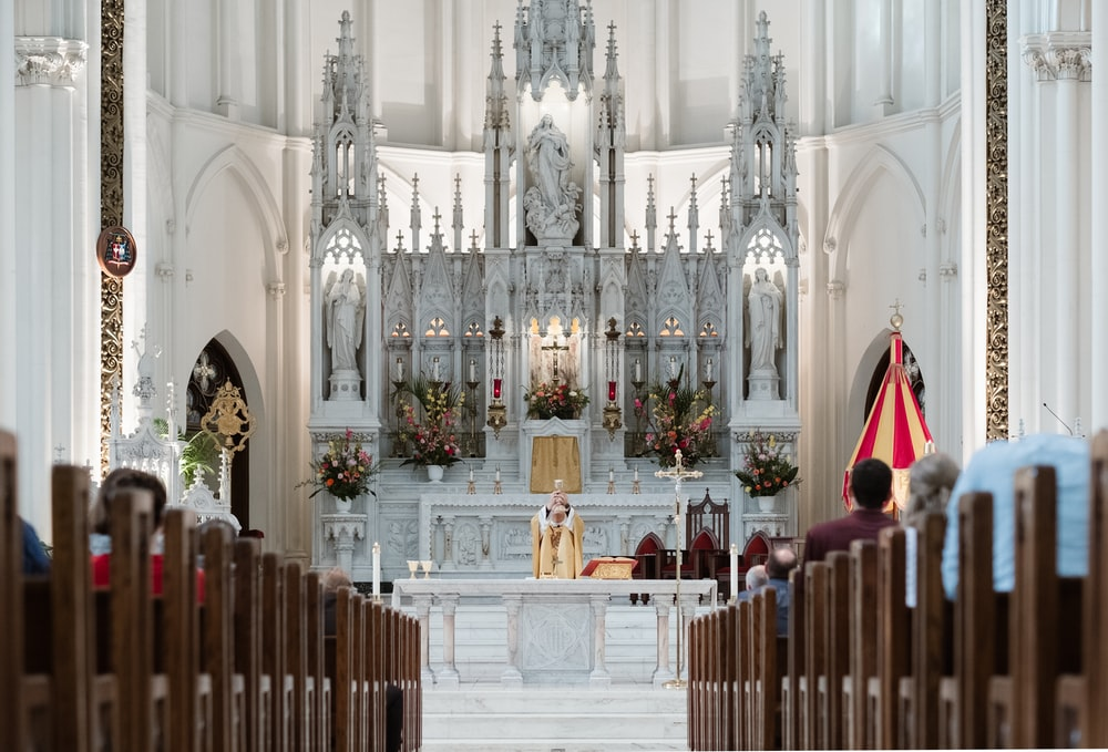 priest standing beside altar in front of sitting people