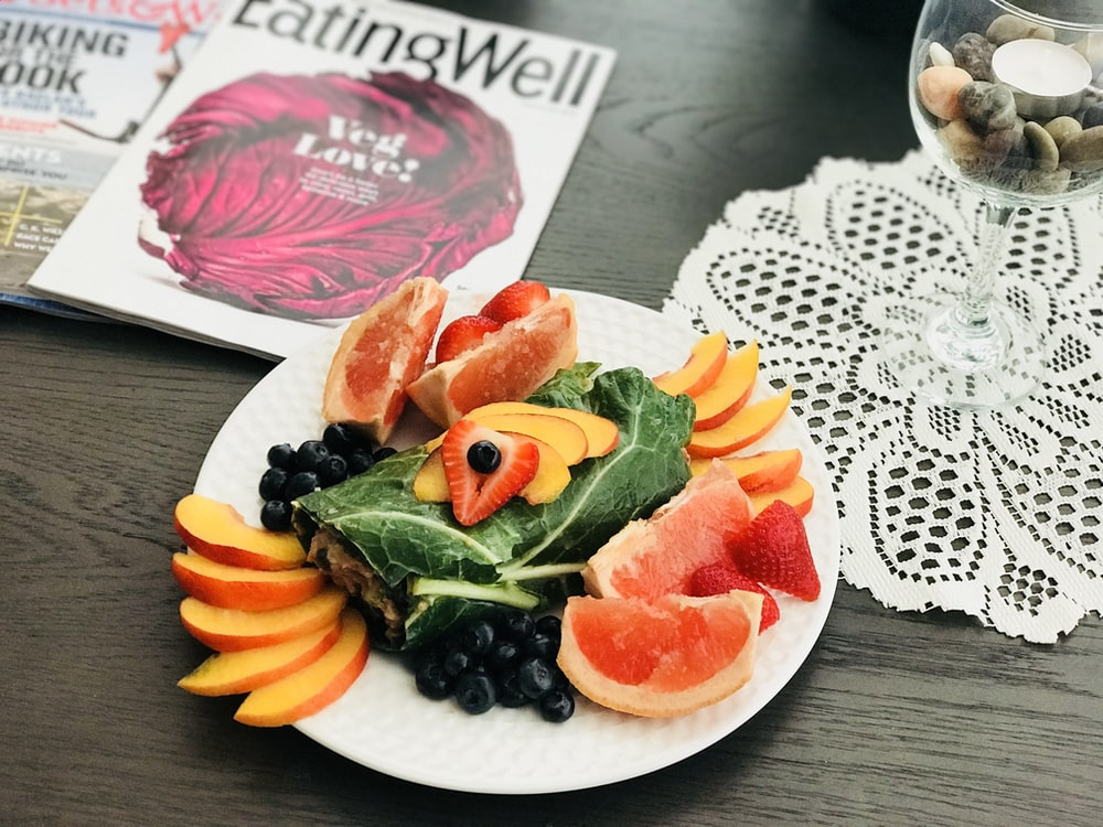fruits on white plate near books