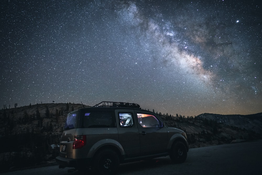 grey SUV parked on side of road under starry night sky