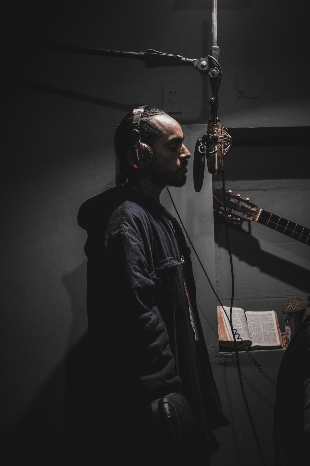 photography of singing man in front of pop filter inside r